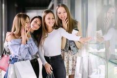 Vier Mädchen, die im Einkaufszentrum kaufen lizenzfreies stockbild