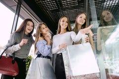 Vier Mädchen, die im Einkaufszentrum kaufen stockbilder