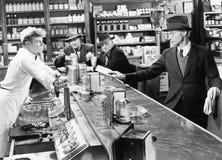 Vier Männer an einem Getränkespender (alle dargestellten Personen sind nicht längeres lebendes und kein Zustand existiert Liefera Lizenzfreies Stockfoto