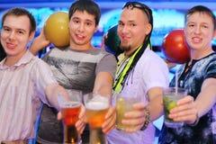Vier Männer halten Kugeln und Gläser im Bowlingspiel an Stockbild