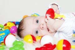 Vier-maanden baby onder speelgoed Stock Foto's
