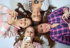 Vier Mädchen, die auf dem Fußboden mit Mobiltelefonen liegen Lizenzfreie Stockfotografie
