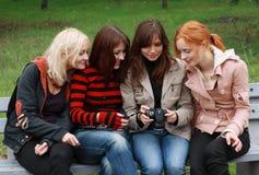 Vier Mädchen, die Spaß mit einer Digitalkamera haben Stockfotografie
