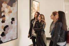Vier meisjesvrienden die het moderne schilderen in kunstgalerie bekijken stock fotografie