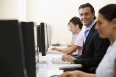 Vier mensen in computerzaal Stock Afbeeldingen