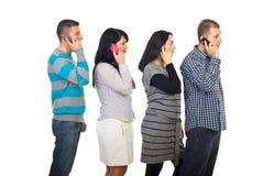 Vier mensen in een lijn die door cellphones spreekt stock afbeelding