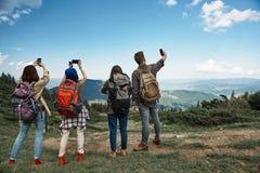 Vier mensen fotograferen bergen met mobiles royalty-vrije stock afbeelding
