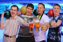 Vier mensen houden ballen en glazen bier Royalty-vrije Stock Afbeeldingen