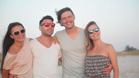 Vier mensen met wilde toothy glimlachen die tijd doorbrengen samen aan de kust tijdens winderig weer en van de zonsondergang geni stock video