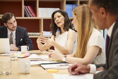 Vier mensen op een bedrijfsbestuurskamervergadering royalty-vrije stock afbeelding