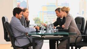 Vier mensen tijdens een commerciële vergadering stock footage