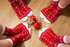 Vier mensenbenen die rode die sokken met Kerstmisornament dragen rond kaarsen op de vloer wordt geplaatst royalty-vrije stock foto