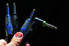 Vier 6,3 Millimeter-Steckfassungsmonoaudioverbindungsstücke, drei gerade und eins geangelt gehalten in der linken Hand auf dunkle Stockfoto