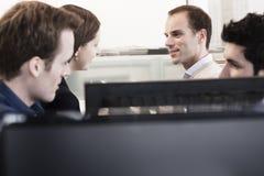 Vier Mitarbeiter, die im Büro durch die Computermonitoren sitzen und sich besprechen stockfoto