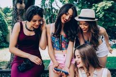 Vier mooie jonge meisjes die de foto's bekijken Royalty-vrije Stock Foto's