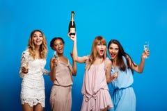Vier mooie meisjes die bij partij over blauwe achtergrond rusten royalty-vrije stock afbeeldingen