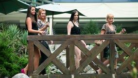 Vier mooie vrouwen die in hoge hielen over houten brug lopen stock video