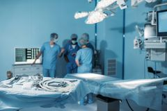 vier multi-etnische chirurgen in werkende ruimte met hulpmiddelen Stock Foto