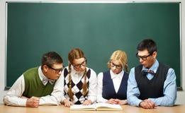 Vier nerds die boek lezen Stock Afbeeldingen
