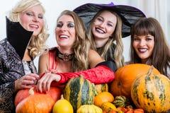 Vier nette Frauen, die zusammen Halloween feiern lizenzfreies stockbild