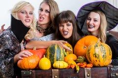 Vier nette Frauen, die zusammen Halloween während der Kostümpartei feiern lizenzfreies stockfoto