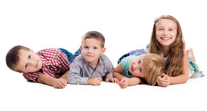 Vier nette Kinder, die auf dem Boden liegen lizenzfreie stockfotografie