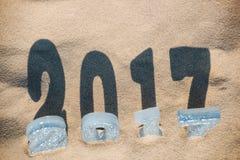 Vier neues Jahr ` s Zahlen sind im Sand auf dem Strand, oder Küste, warf einen großen Schatten aus den Grund Stockbilder