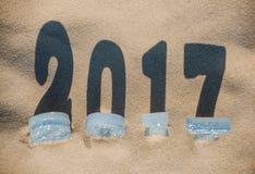 Vier neues Year& x27; s-Zahlen sind im Sand auf dem Strand oder der Küste, Lizenzfreies Stockfoto