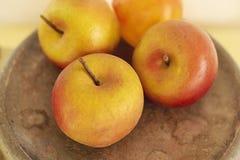 Vier orange Äpfel auf einer Platte Lizenzfreie Stockfotografie