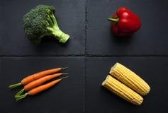 Vier organisches Gemüse auf Schieferplatte stockfoto