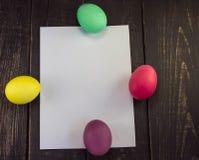 Vier Ostereier mit leerem Papier auf Holztisch Lizenzfreies Stockfoto