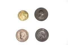 Vier oude muntstukken op witte achtergrond stock afbeelding