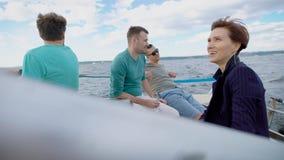Vier oude vrienden die enkel op een jacht zitten, varend het overzees, casualy nippend champange en over materiaal babbelen stock video