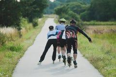 Vier oudere mensen die op rolschaatsen in lijn berijden stock foto