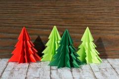 Vier Papierorigami Weihnachtsbäume auf einem hölzernen Hintergrund Lizenzfreie Stockbilder