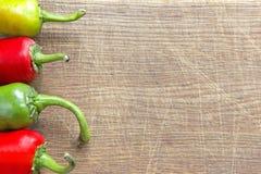 Vier Paprika pepers an Bord Stockbilder