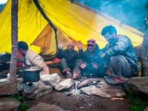 Vier personen die een brand in de koude, beeld van Manali, Himachal Pradesh, India in januari 2015 hebben stock foto