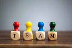 Vier Pfandfigürchen, Teamkonzept, Tabelle, grauer Hintergrund Lizenzfreie Stockbilder