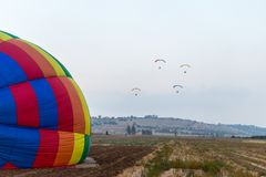 Vier Piloten auf motorisierten Fallschirmen fliegen über den Flugplatz am Heißluftballonfestival lizenzfreies stockbild
