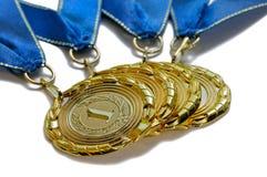 Vier Preismedaillen Goldfarbe mit blauen Bändern Stockfotos