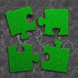 Vier puzzels van groene grastextuur, op droge gebarsten grijze landachtergrond, hoge hoekmening royalty-vrije stock afbeelding
