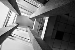 Vier rechthoekige kolommen, trappen met metaal verchromen traliewerk, helder licht van het venster, abstract perspectief in archi Stock Afbeelding