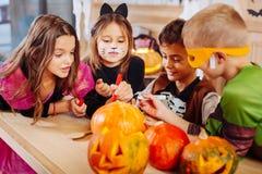 Vier regten strahlende Kinder mit den gemalten Gesichtern auf, die Halloween-Kostüme tragen stockbild