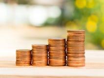 Vier Reihen des steigenden goldenen Stapels des Wachstums prägt mit grünem Naturhintergrund Wachsendes und Rettungsgeldkonzept Lizenzfreie Stockbilder