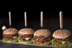 Vier Rindfleischburger mit Pilzen, Mikrogrüns, roter Zwiebel, Spiegeleiern und Soße der roten Rübe auf hölzernem Schneidebrett lizenzfreie stockfotografie