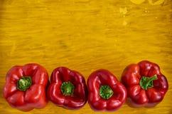 Vier rode groene paprika's sluiten omhoog op houten gele achtergrond met exemplaarruimte De groene paprika's op houten gele textu Royalty-vrije Stock Foto