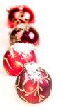 Vier rode snuisterijen van Kerstmis op sneeuw Royalty-vrije Stock Foto's