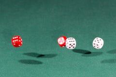 Vier rot und weiß würfelt das Fallen auf eine grüne Tabelle stockbilder