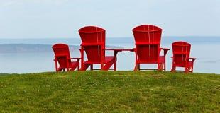 Vier rote Adirondack-Stühle Stockfotografie