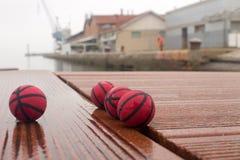 Vier rote Basketbälle auf den Platten des stumpfen Tages des Hafens stockfotografie